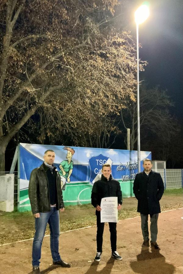 v.l. Marcel Huhla (Abteilungsleiter Fußball), Florian Schleußner (Auszubildender der Stadt Calbe) und Bürgermeister Sven Hause nehmen die neue Flutlichtanlage auf dem Sportplatz Heger in Betrieb.   Foto: Stadt Calbe