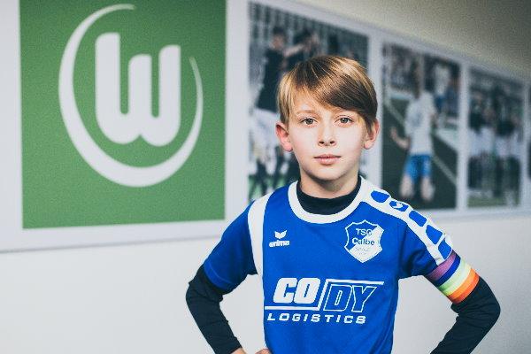 Der calbenser F-Jugendkapitän Jakob Sieche im TSG-Trikot mit Regenbogenbinde in den Räumlichkeiten des VfL Wolfsburg. | Foto: Verein